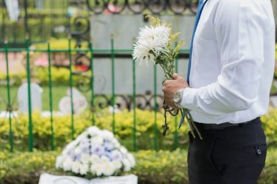 Religious man at a funeral carrying flowers and a cross