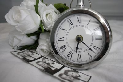 Black and white photo of flowers, clock and photos of a loved one who passed away